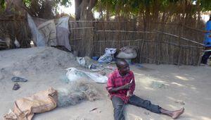 Fischer flickt Fischnetz in Malawi